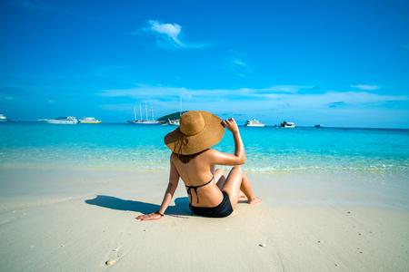 Achtermening van jonge vrouwenreiziger met zwarte bikini en hoed sittng op het strand bij similan eilanden in Andaman-overzees bij de provincie van Phang Nga dichtbij Phuket en Krabi in zuidelijk van Thailand. Zomer Relax Stockfoto - 94692942