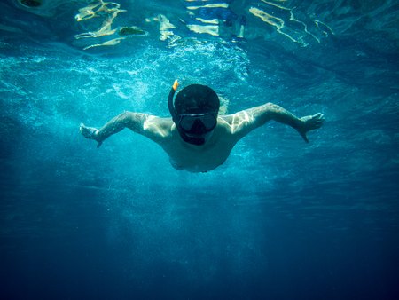 Underwater view of a young diver man swimming under blue sea under the surface with snorkelling mask for summer vacation at Similan islands, Andaman sea, Phang Nga near Phuket nad Krabi in Thailand. 스톡 콘텐츠