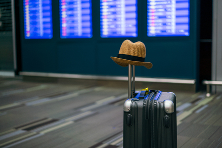 Suitcases with hipster hat in airport departure lounge, Boarding times in background, summer vacation concept, traveler suitcases in airport terminal waiting area. 스톡 콘텐츠