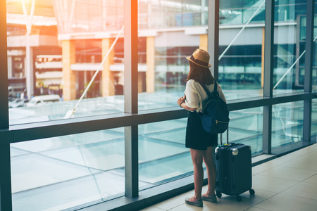 Young asian woman with baggage looking through the window of an airport departure lounge