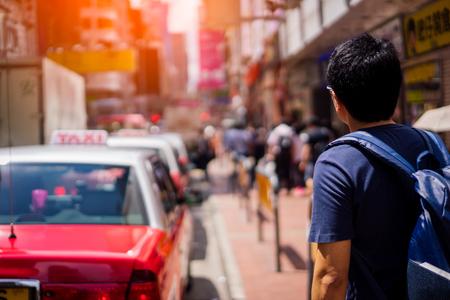 Young asian traveler waiting taxi for transportation at Hong Kong city
