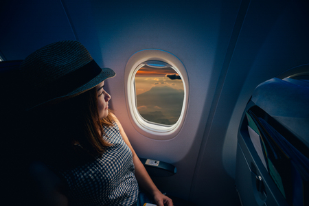 Young asian woman traveler looking view at window in airplane with happiness and relaxing