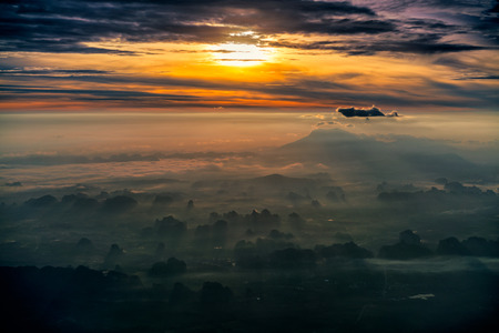 Aerial view of beautiful landscape in the mountains at sunrise. View of foggy hills covered by forest.