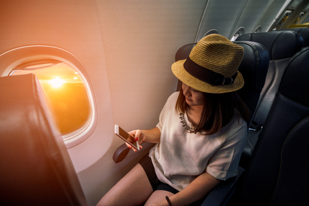 Young asian woman traveler using smartphone in airplane with happiness and relaxing