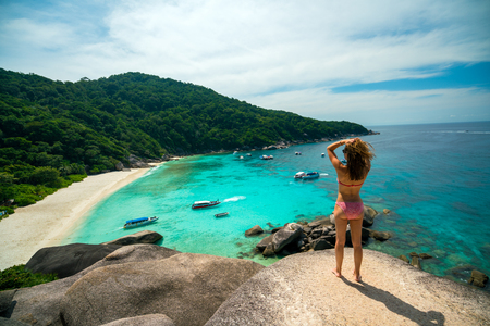 Rear view of young sexy woman traveler with bikini relaxing on viewpoint at similan islands in Andaman sea at Phang Nga province near Phuket and Krabi in southern of Thailand. Summer Relax