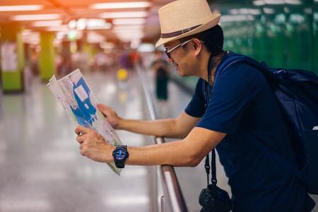 Young man asian traveler looking map at Hong Kong subway station MTR 스톡 콘텐츠