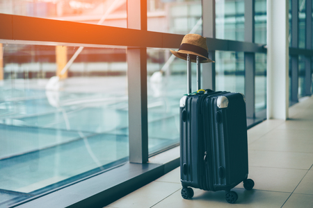 Suitcases with hipster hat in airport departure lounge, summer vacation concept, traveler suitcases in airport terminal waiting area.