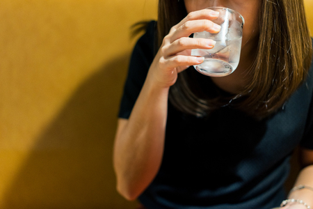 Woman drinking cold fresh water from glass at restaurant