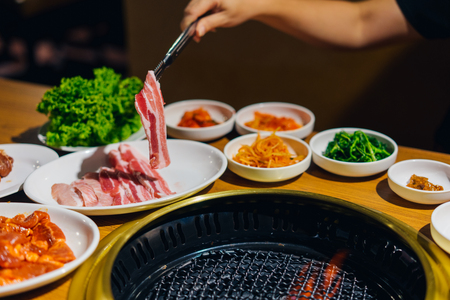일식 또는 한식 야키니쿠 스타일의 레스토랑. 일본 야키니쿠에 쇠고기 슬라이스 구이 데 손 여자. 스톡 콘텐츠