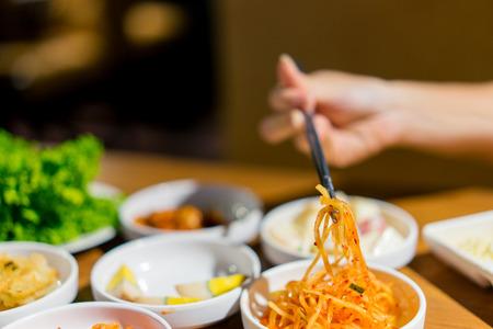Woman hand holding chopsticks for eating Kimchi salad in restaurant. Korean food traditional Kimchi
