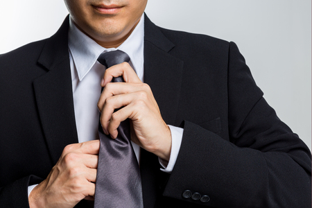 Young happy businessman with black suit adjusting his necktie isolated on white background Standard-Bild