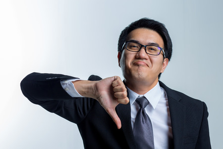 Young asian businessman with suits showing thumbs down isolated on white background 스톡 콘텐츠