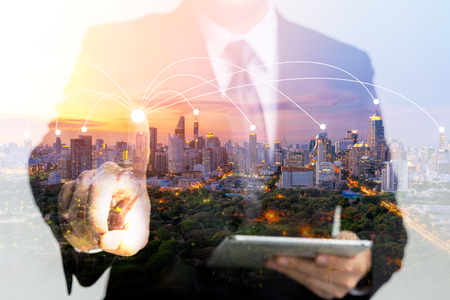 Double exposure of a businessman using a tablet and finger touch screen. Network connecting concept 스톡 콘텐츠