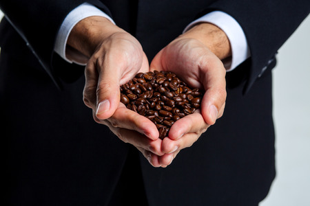 Businessmans hands holding fresh roasted coffee beans isolated on white background