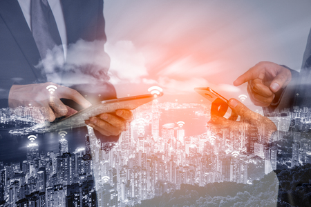 Double exposure of Hong Kong cityscape view form The Peak Hongkong and network connection concept, Wifi at business district and hand of business people using tablet and smartphone.