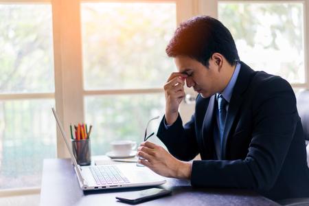 Épuisé fatigué jeune homme d'affaires asiatique travaillant sur ordinateur portable au bureau, massant le pont du nez et tenant des lunettes.