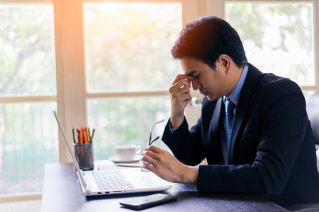 Exhausted tired young asian businessman working on laptop at office, massaging nose bridge and holding glasses. Archivio Fotografico