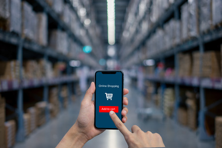 Mans hand shows mobile smartphone with online shopping screen in vertical position for shopping on smart phone.