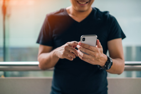 Man using smartphone with happiness while standing at Skytrain Stock Photo