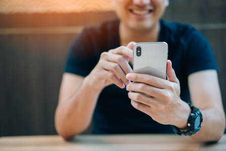 Young businessman smiling and using smartphone in restaurant