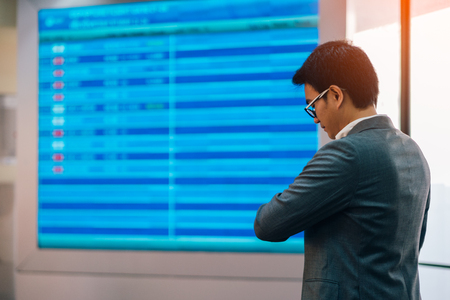 Young asian businessman standing near airline schedule and looking at his watch