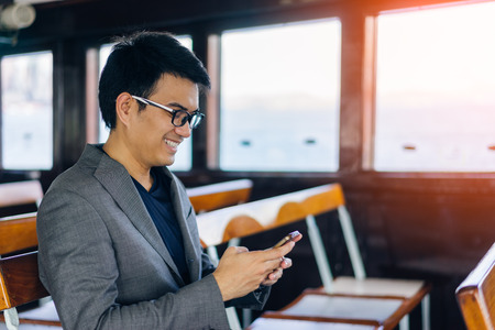 Young asian businessman with suits using smartphone with happiness on Hong Kong ferry crossing in Victoria Harbor at Hong Kong downtown city Stock Photo