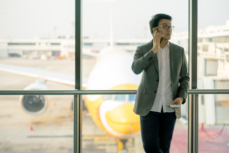 Young asian businessman standing and using smartphone at waiting area in international airport