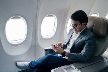 Young asian businessman with suit sitting in business first class seat via using smartphone with happiness Stock fotó - 97925784