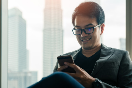 Young asian businessman using smartphone with happiness in hotel with background of cityscape in Kuala Lumpur Panorama at twilight at Kuala Lumpur, Malaysia