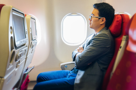 Young asian businessman with suits sitting on seat in airplane near the window and sleeping with relaxing Stock Photo