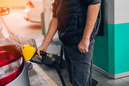 Man holding pumping gasoline fuel in car at gas station