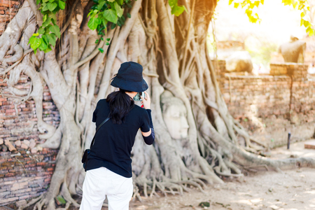 Young woman traveler using smartphone take a photo at the Head of the Buddha, with tree trunk and roots growing around it. Wat Mahathat temple, Ayutthaya near Bangkok Thailand. Traveling in Ayutthaya