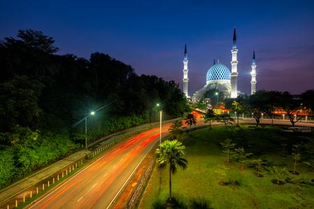 Sunrise scene of light trails of car on the road into Blue Mosque or Sultan Salahuddin Abdul Aziz Shah Mosque location at Shah Alam Selangor near Kuala Lumpur, Malaysia.