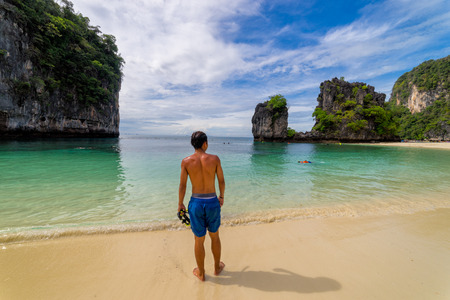 Young man traveler relaxing standing in topical beach on Koh Hong islands in Andaman sea at Krabi near Phuket southern of Thailand 스톡 콘텐츠
