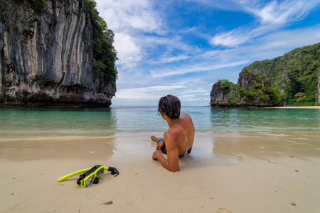 Young man traveler relaxing lying down in tropical beach on Koh Hong islands in Andaman sea at Krabi near Phuket southern of Thailand 스톡 콘텐츠