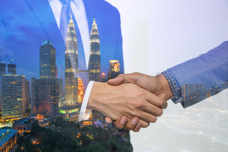 Double Exposure of a businessman handshake on Kuala lumpur cityscape skyscraper Malaysia background. 스톡 콘텐츠