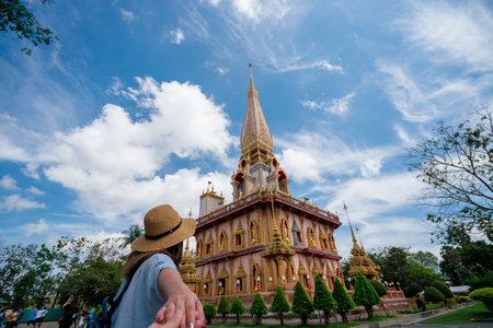 Young woman traveler holding hand man into beautiful pagoda in Wat Chalong or Chalong temple at Phuket town, Thailand. Its most popular thai temple in Phuket Thailand.