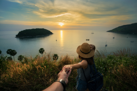 Romantic scene of young love couple holding hand in view point look sunset at Promthep Cape Phuket, Thailand. 스톡 콘텐츠