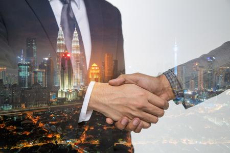 Double Exposure of a businessman handshake on Kuala lumpur cityscape skyscraper Malaysia background. 版權商用圖片