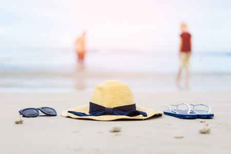 Flip-flops, beach hat and sunglasses on the sand. Summer vacation concept Stock Photo