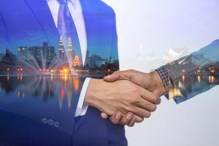 Double Exposure of a businessman handshake on Kuala lumpur cityscape skyscraper Malaysia background. Editorial