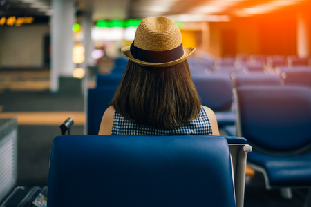 Young woman traveler sitting on chair of passenger in an airport lounge waiting for flight aircraft 스톡 콘텐츠