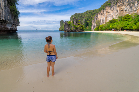 Young women wearing bikini relaxing standing in topical beach on Koh Hong islands in Andaman sea at Krabi near Phuket southern of Thailand