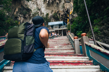 Young man traveler with backpack traveling into Batu Caves Lord Murugan Statue and entrance at Hindu Temple near Kuala lumpur Malaysia