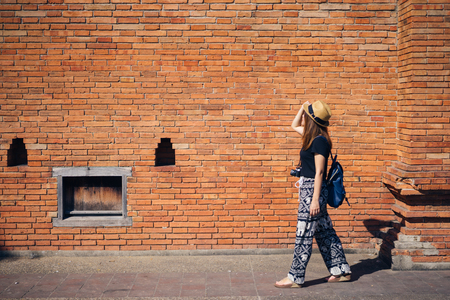 Young asian woman traveler with hat and bag travelling to Tha Pae Gate at the old Chiangmai city in Chang Mai, Thailand.