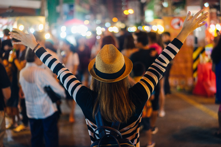 Young asian woman traveler backpacker with hat and bag traveling to Chiang Mai night walk street market at Chiang Mai Province, Thailand. 版權商用圖片