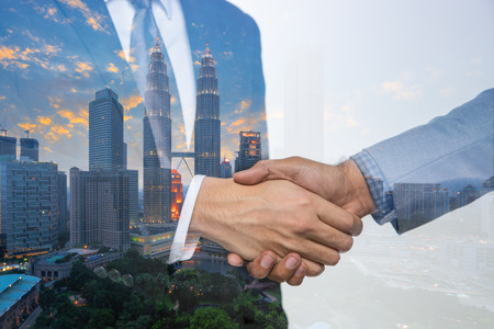 Double Exposure of a businessman handshake on Kuala lumpur cityscape skyscraper Malaysia background. 에디토리얼