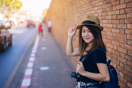 Young asian woman traveler with hat and bag using film camera traveling into  Tha Pae Gate at the old Chiangmai city in Chang Mai, Thailand. 版權商用圖片