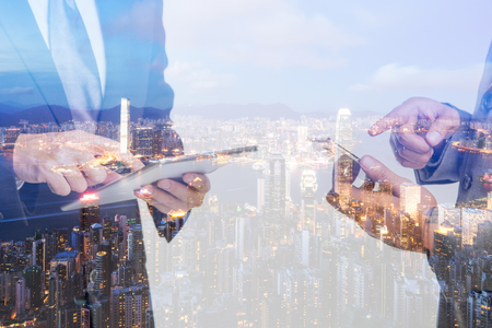 Double Exposure of a businessman use smartphone on the Hong Kong skyscraper background.