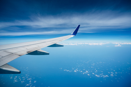 Beautiful view from the inside airplane of blue sky and clouds with airplane wing